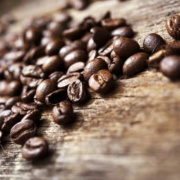 Coffee Beans on Aged Wood Table Closeup.